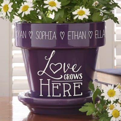 "Brighten Mom's day with this colorful personalized ""Love Grows Here"" flowerpot...a Mother's Day gift she'll love!"