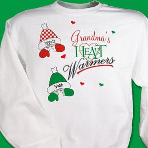 Grandma's heart will be overfilled with love and warmth each time she wears this personalized Christmas sweatshirt. <br/><br/>Our custom Heart Warmers sweatshirt can be personalized with any title (up to 16 letters) and decorated with up to 30 hat and mitten combinations
